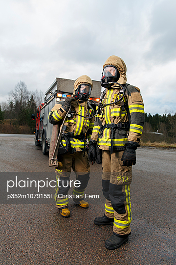 Sweden, Sodermanland, Tumba, Firefighters wearing gas mask standing on road