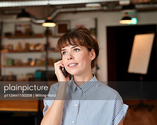 Junge Frau telefoniert im Büro - p1124m1150208 von Willing-Holtz