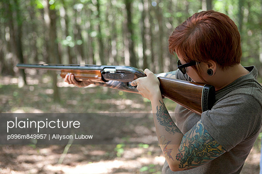 Tatooed woman shooting shotgun in forest.