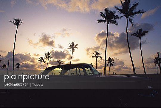 Classic American car under sunset and palm trees