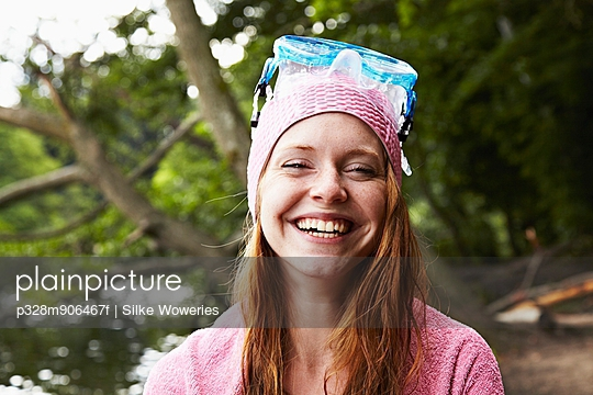 Portrait of happy woman wearing bathing cap and snorkel, lake in background