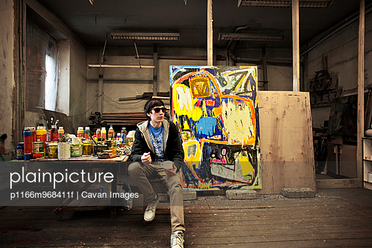 Artist Sitting By Painting In Studio