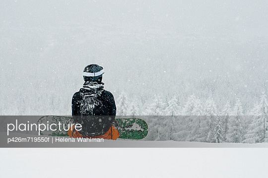 Rear view of a person sitting with snowboard