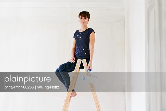 Junge Frau sitzt auf Leiter mit Farbrolle - p1124m1160256 von Willing-Holtz