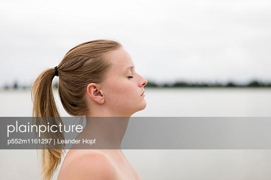 Junge Frau mit geschlossenen Augen am See - p552m1161297 von Leander Hopf