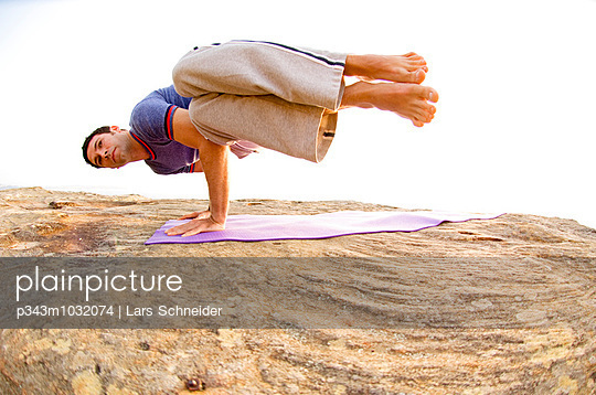 James Fellows practicing yoga on a rocky outcrop above the Pacific Ocean at North Curl Curl, one of Sydneys Northern Beaches. Sy