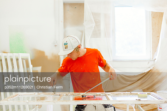 Young man preparing window frame for painting