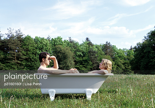 couple sitting in a bathtub outdoors in the grass
