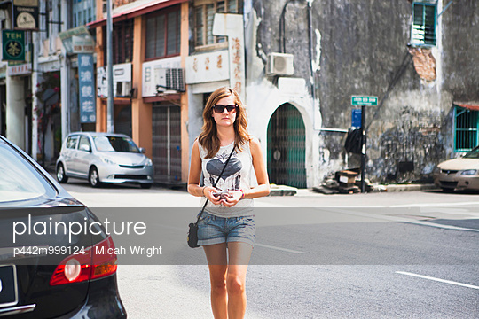 A young female tourist walks on the street in Georgetown, Little India and Chinatown areas; Penang, Malaysia