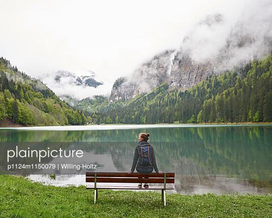 Frau sitzt auf Bank am Lac de Montriond - p1124m1150079 von Willing-Holtz