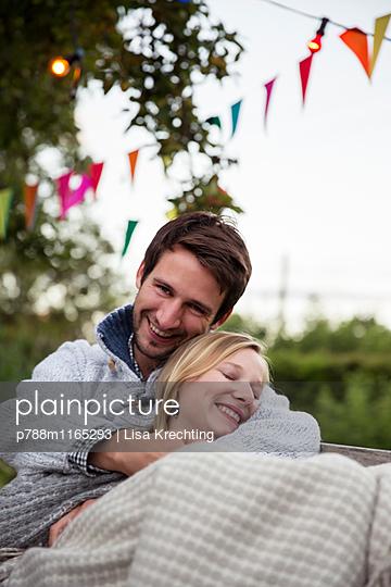 Junges Paar kuschelt auf einer Bank - p788m1165293 von Lisa Krechting