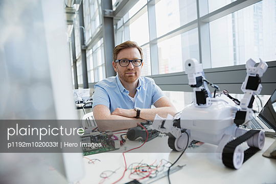 Portrait of confident engineer at desk with robot