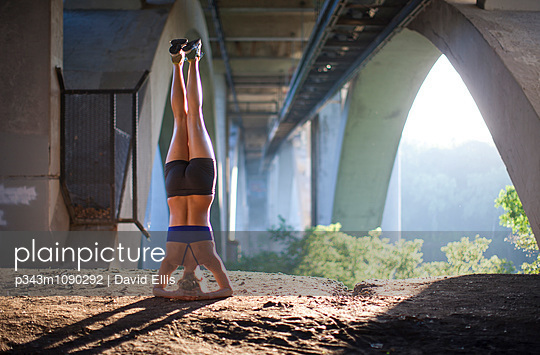A woman does a headstand in the morning sunlight in an urban setting underneath a bridge.