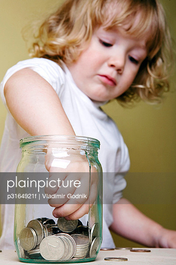 young boy taking money out of jar