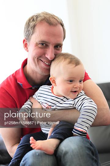 Vater hält Tochter im Arm - p1258m1158887 von Peter Hamel