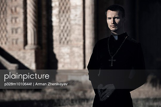 Catholic priest in shadow of church