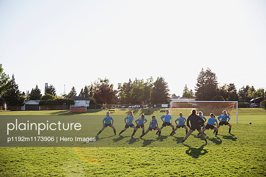 Coach and middle school girl soccer team stretching at practice on sunny field