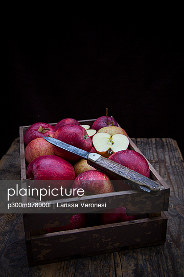 Wooden box of red apples and a pocket knife in front of black background