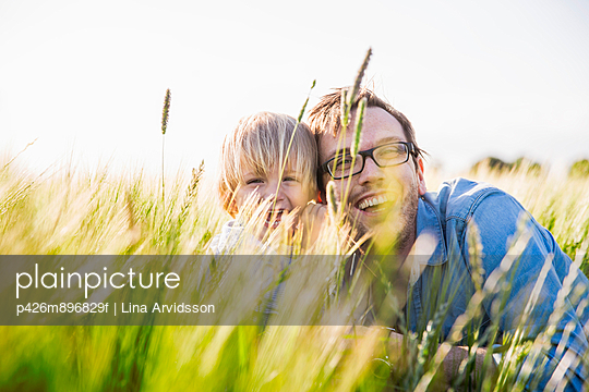 Smiling father and son in field