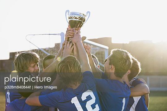 Soccer team lifting trophy together.