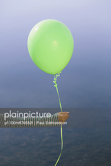 Nine year old girl holding green balloon, sitting by waters edge
