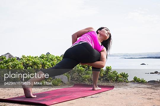 Woman practicing yoga pose on beach, Hawea Point, Maui, Hawaii, USA