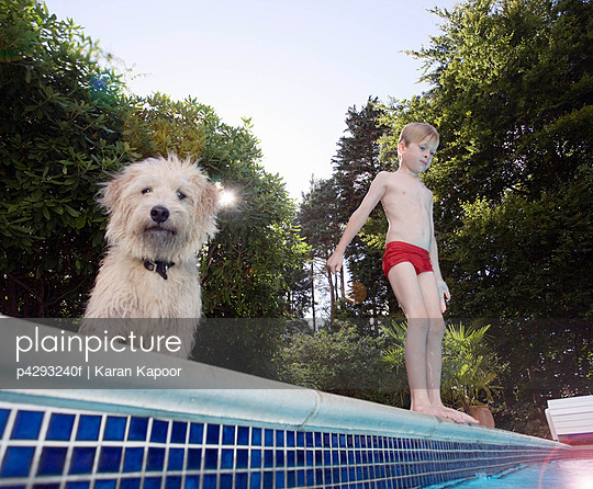 Boy with dog about to jump into pool