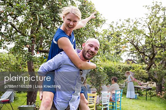 Junges Paar albert im Garten herum - p788m1165328 von Lisa Krechting