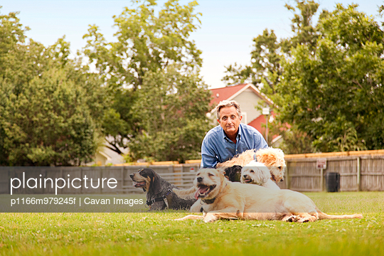 Older man in yard with dogs