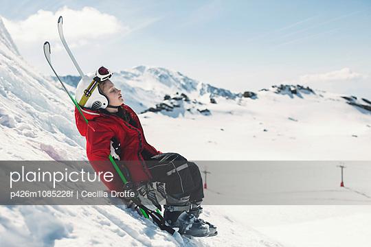 Side view of girl in ski-wear relaxing on ski slope