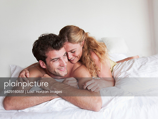Smiling couple laying in bed together