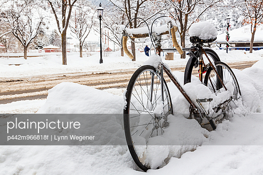 A road bike covered with snow sits by the side of a snowy road waiting for spring; Glenwood Springs, Colorado, United States of America
