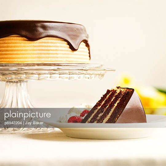 slice of chocolate cake and a cake with chocolate frosting