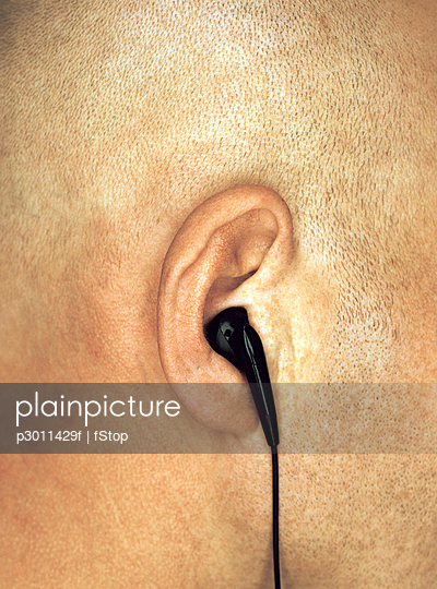 Close-up of man\'s ear with earphone