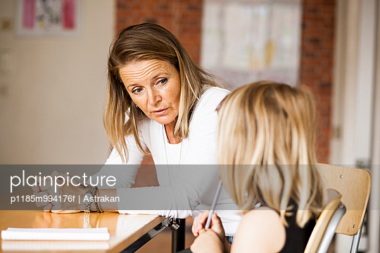 Mature teacher talking with girl in classroom