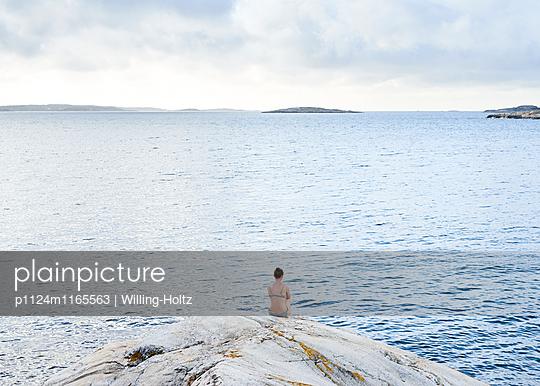 Frau sitzt auf Felsen und blickt aufs Meer - p1124m1165563 von Willing-Holtz