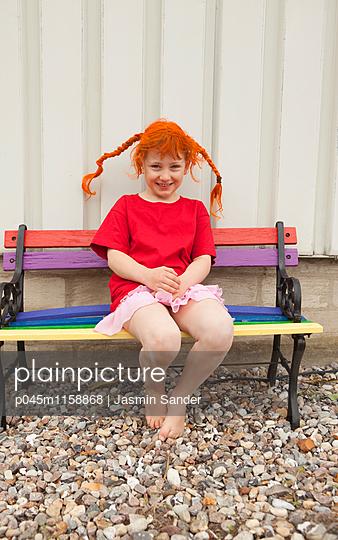 Kleine Pipi Langstrumpf sitzt auf Parkbank - p045m1158868 von Jasmin Sander