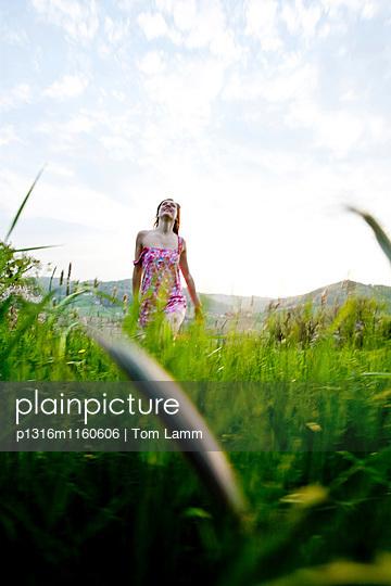 Junge Frau geht durch hohes Gras, Riegersburg, Steiermark. Österreich - p1316m1160606 von Tom Lamm