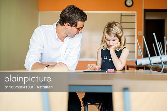 Male teacher watching girl using digital tablet in classroom