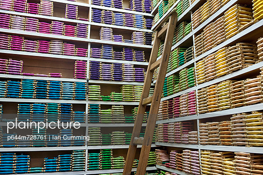 Rows of shelves with colourful textiles arranged by colour and shade; Fez, Morocco