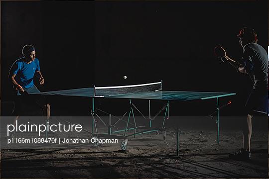 Two men playing table tennis at night