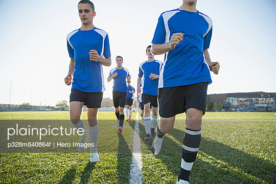 Soccer team running together on field.