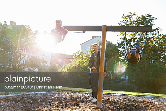 Sweden, Sodermanland, Arsta, Father with son (4-5) and daughter (2-3) swinging on playground at sunlight