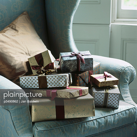 Silver and gold wrapped Christmas presents on an armchair