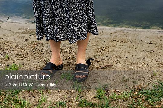 Frauenfüße in Sandalen am Ufer - p1212m1159122 von harry + lidy
