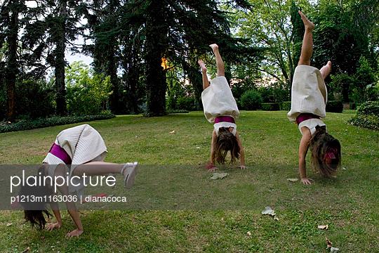 Mädchen machen Handstand im Grünen - p1213m1163036 von dianacoca