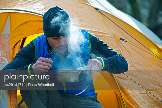 Man cooking food by camping tent
