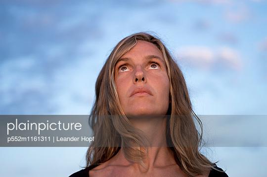 Junge Frau blickt nach oben  - p552m1161311 von Leander Hopf