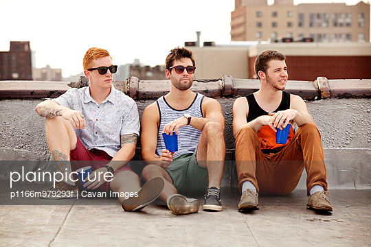 Three Male Friends Sitting On City Rooftop
