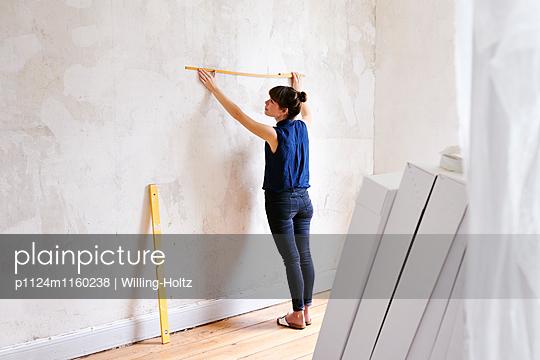Junge Frau misst Wand in neuer Wohnung - p1124m1160238 von Willing-Holtz